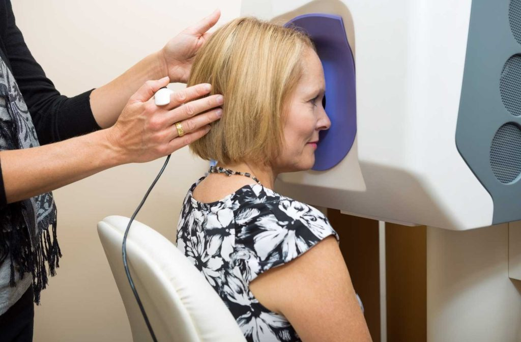 Woman wearing black and white enjoying thorough eye exam leaning head against advanced retinal imaging machine with purple trim