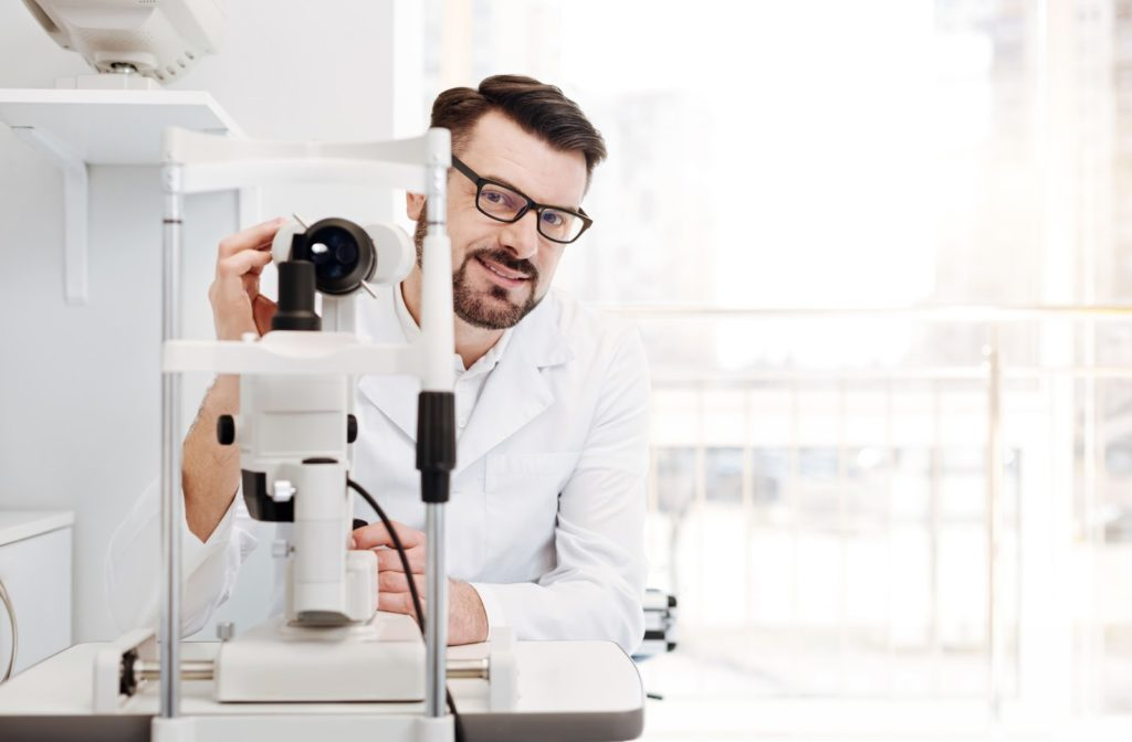 Smiling male optometrist with glasses adjusting an eye test machine