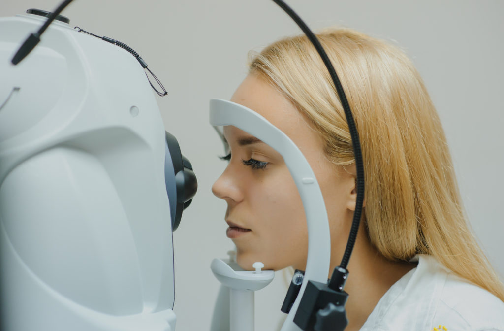 A young woman having her eye examined through OCT