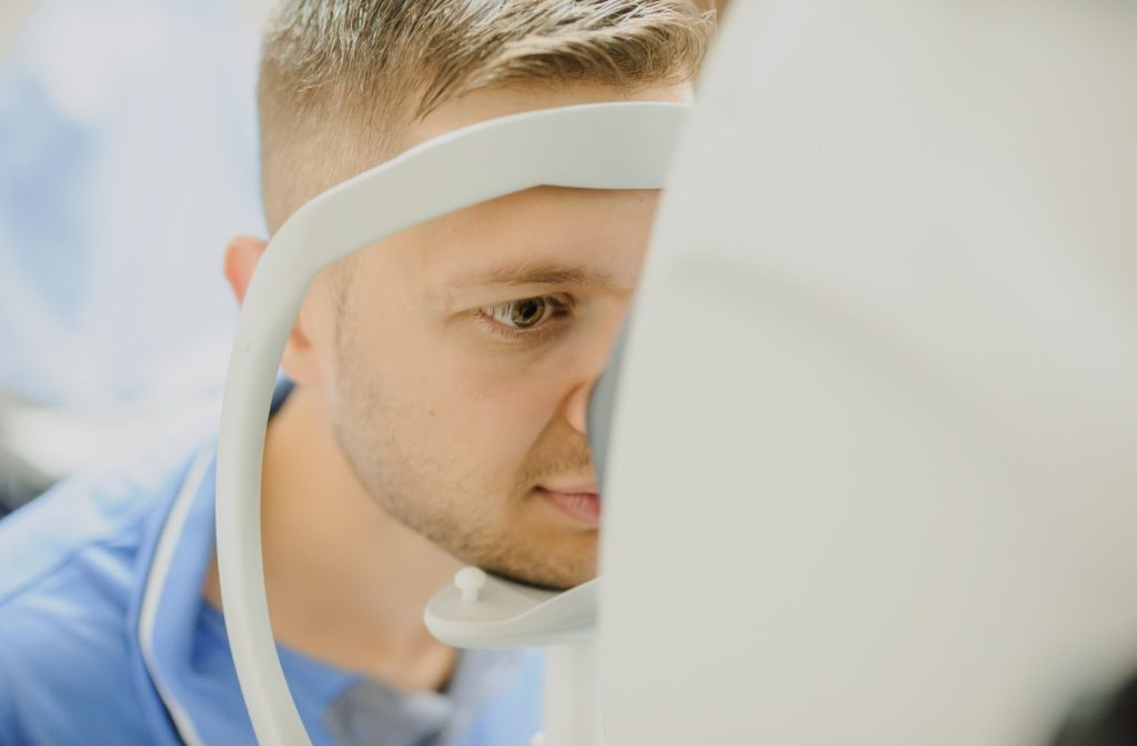 A young man having OCT used during an eye exam