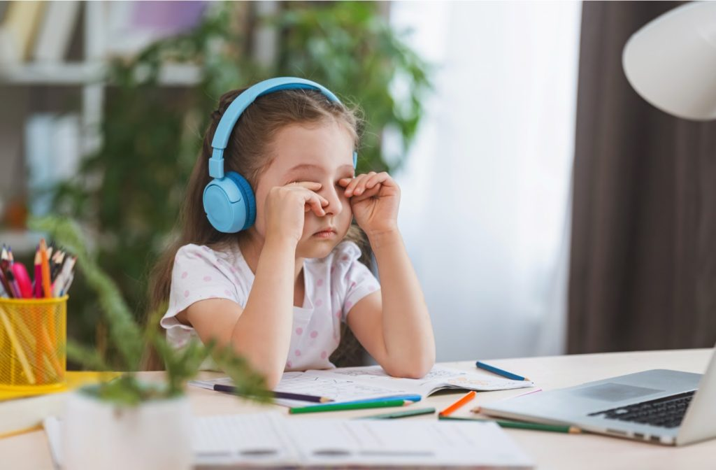 Young girl suffering from dry eye as she works on laptop to finish homework